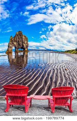 Pair of red deck chairs set on the beach in front of Rock Hvitsercur. Northern coast of Iceland. Concept of extreme northern tourism