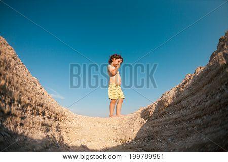 The Boy Walks Along The Sandy Beach.