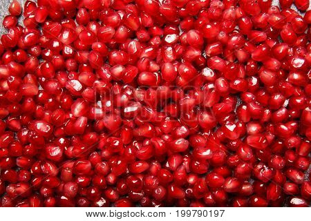 A beautiful bright red background made of juicy, fresh, ripe, sour pomegranate seeds. Agriculture, organic, rustic concept. Exotic fruits with nutritious seeds full of vitamins.