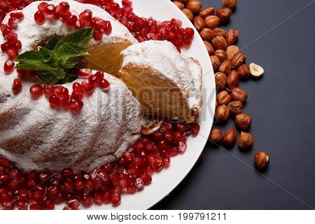 Close-up of powdered cake with hazelnuts, pomegranate grains and decorative mint on the purple background. A portion of ring cake with crunchy nuts and sour berries. Cafeteria dessert concept.