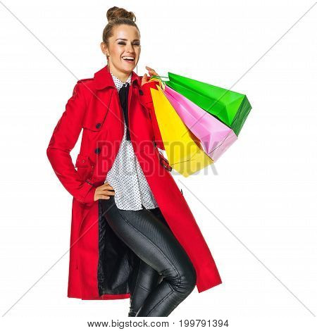 Keep the autumn bright. Full length portrait of smiling stylish woman in red coat isolated on white background with shopping bags