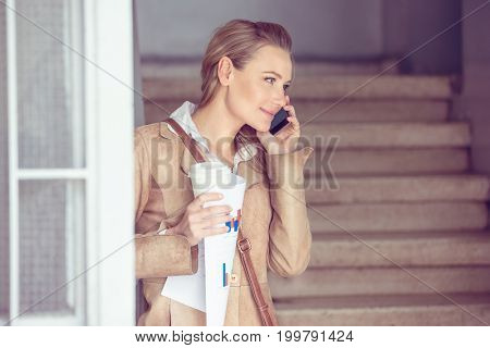Portrait of a beautiful blond student girl talking on the phone and drinking coffee, using smart technology for work and communication, modern life of young people