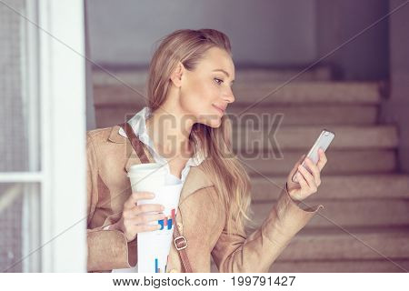 Beautiful young businesswoman texting and drinking coffee, working on the smartphone, modern computer technologies in business life
