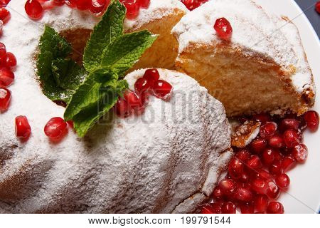 Close-up of fresh, powdered cake and juicy garnet seeds on a white plate background. A portion of marble cake with green mint and red berries. Freshly baked confectionery pastry.