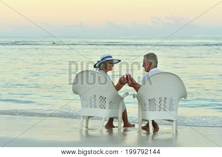 Senior couple resting on beach  in chairs toasting