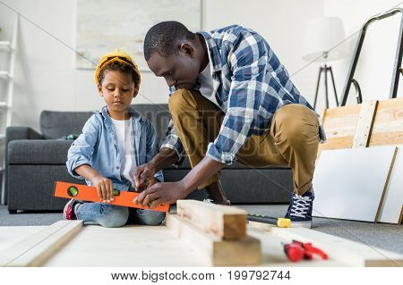 African-american Father Teaching His Son How To Use Tools
