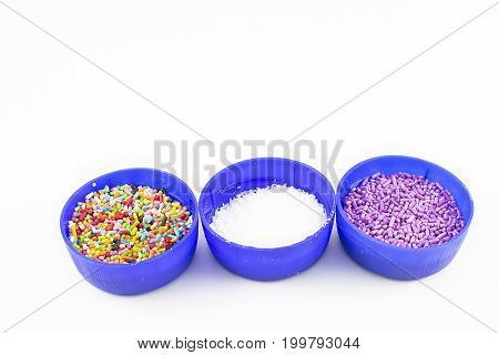 Blue tapers with dragees of different colors and shredded coconut. White background.