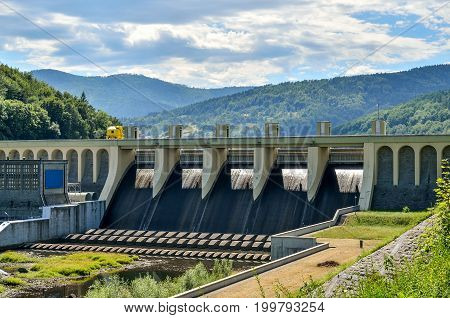 Summer industrial landscape. Water reservoir against the background of beautiful mountains.