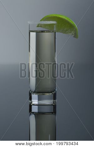 Alcoholic cocktail in shot glass. Hot mexican tequila served in a glass with salt and a slice of lime, alcoholic beverages for parties, fervent drinks from Mexica on a dark gray background.