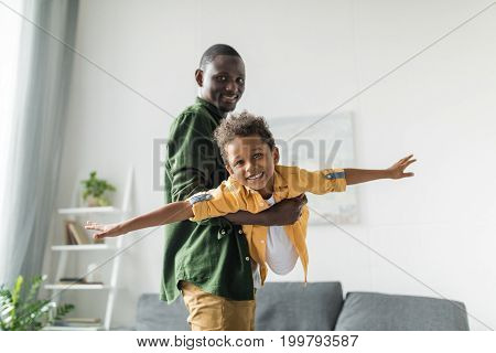 Afro Father And Son Playing At Home, Pretending Airplane