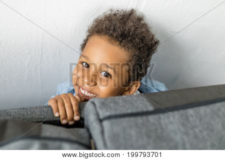 Close-up Shot Of Adorable Smiling Afro Boy Hiding By Sofa