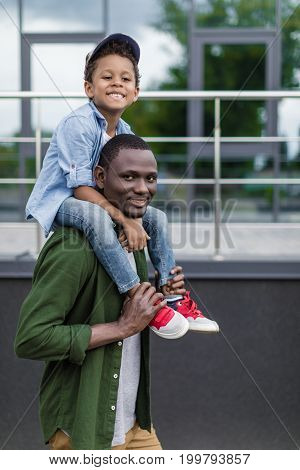little african-american boy piggybacking on father outdoors