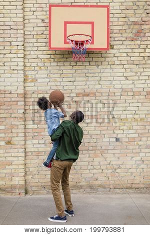 Rear View Of Father And Son Playing Basketball Together