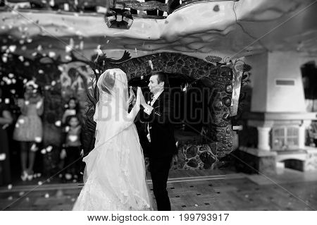 Wedding Couple Dancing Their First Dance In The Restaurant With Confetti On The Floor. Black And Whi