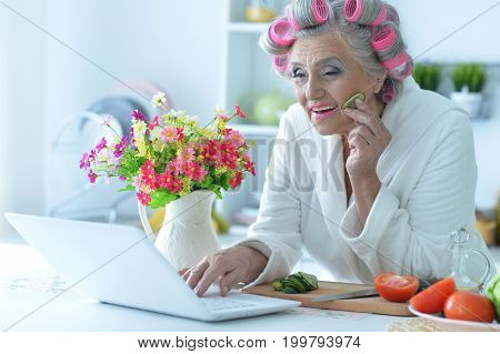 Senior woman with pink hair curlers on head sitting at table and using laptop