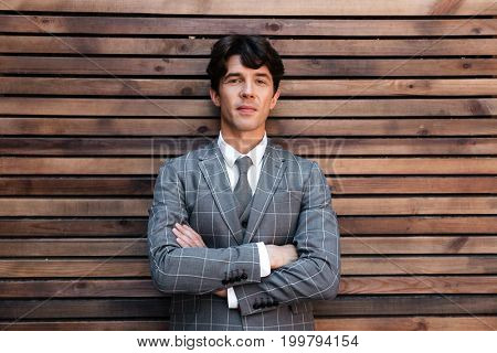 Smiling handsome businessman in suit standing with arms folded against wooden wall