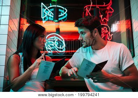 Picture of young multiethnic happy loving couple sitting in cafe looking aside holding restaurant menu.