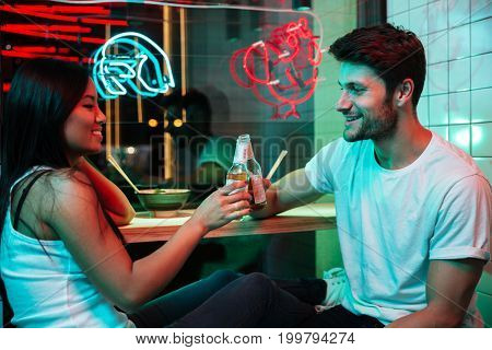 Picture of young multiethnic cheerful loving couple sitting in cafe drinking beer.