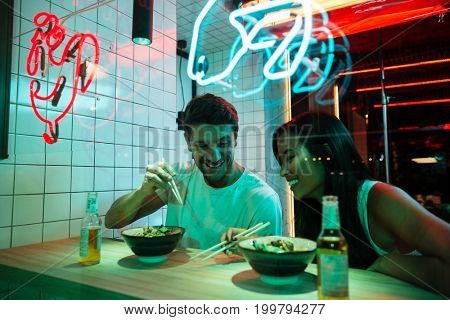Image of young multiethnic cheerful loving couple sitting in cafe looking aside eating.