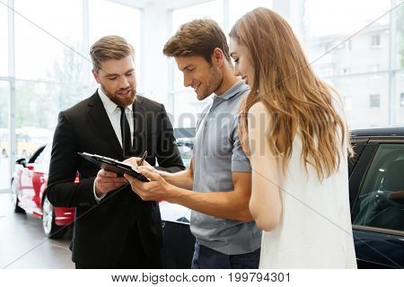 Handsome salesman filing documents with his happy clients at the dealership