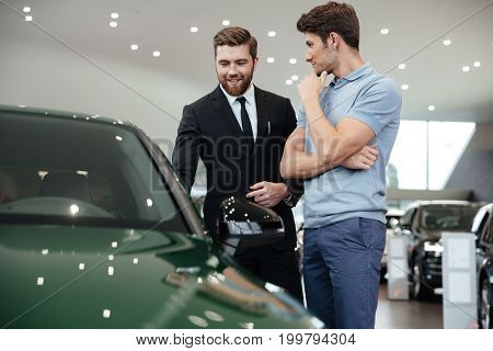 Young male car salesman showing a new car to the customer at the dealership