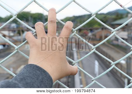 Man grasp the bar of cage with the defocused of city background