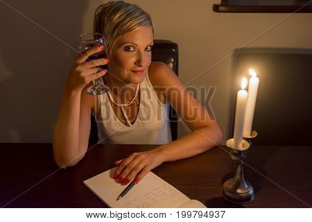 woman celebrates with wine while she writting a letter