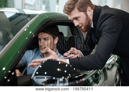 Young man examining a new car with a salesperson at the dealership