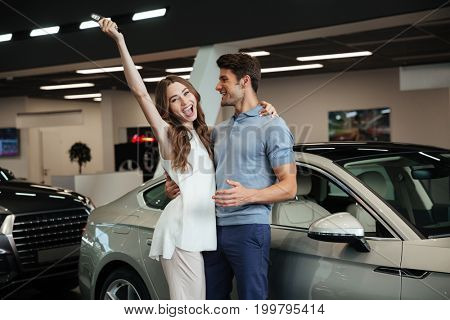 Picture of young loving couple standing near car in car dealership. Looking camera showing keys make winner gesture.
