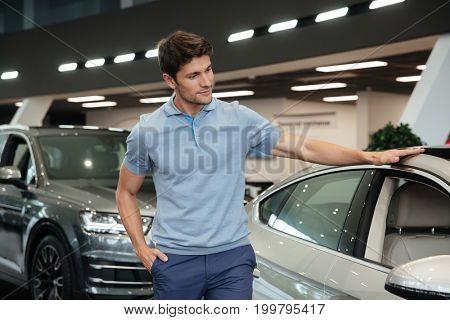 Young man examining and looking carefully at his new car at a dealership