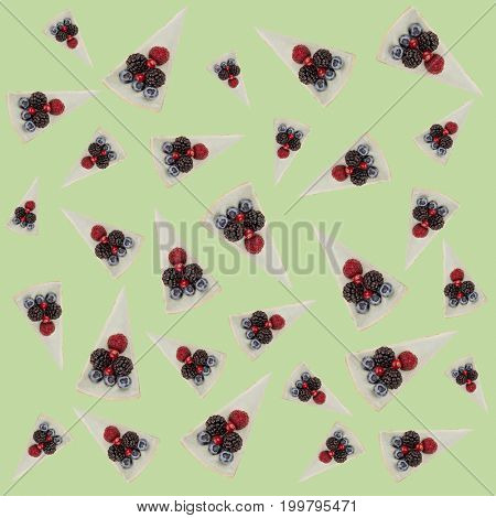 Pattern of blue cheesecakes with different tasty berries isolated over green