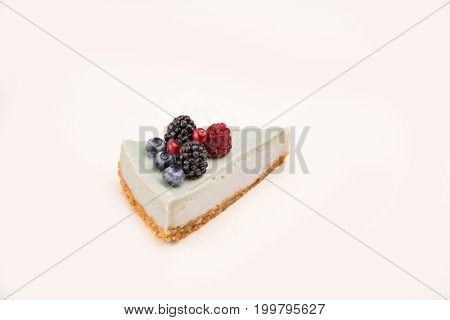 Side view of blue cheesecake with different berries on it isolated over white