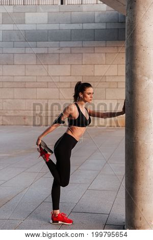 Image of concentrated young sports lady make sport exercises with earphones outdoors.