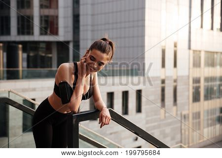 Image of happy young sports woman standing with earphones outdoors and looking aside.