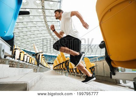 Side view of a young male runner running upstairs at the stadium