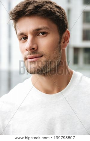 Close up portrait of a handsome young man looking at camera while standing outdoors