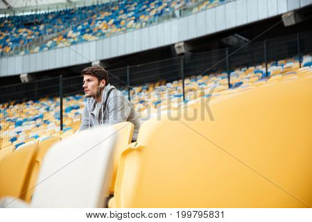 Picture of serious young sports man at the stadium outdoors listening music and looking aside.