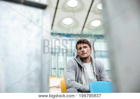 Image of handsome young sports man at the stadium outdoors listening music and looking aside.