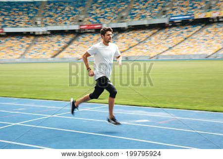 Side view of a young professional sprinter running on racetrack