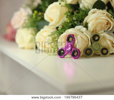 Two Fidget Spinners Pink And Green Toys On White Shelf With Flowers On Background Closeup