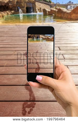 Closely image of female hands holding mobile phone with photo camera mode on the screen. Cropped image of footprints on the wooden floor behind it swimming pool with artificial waterfall on a beautiful resort in Egypt
