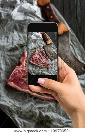 Photographing food concept - woman takes picture of raw dry aged t-bone steaks for grill with fresh herbs and cleaver. Top view