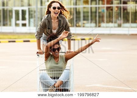 Two young happy women in sunglasses having fun shopping trolley race outdoors