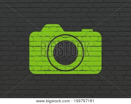 Travel concept: Painted green Photo Camera icon on Black Brick wall background
