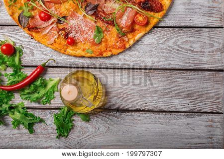 Italian cuisine. A view from above on a tasty pepperoni pizza with a bottle of olive oil and salad leaves. Delicious bright dish on a rustic wooden table background. Cooking concept. Copy space.