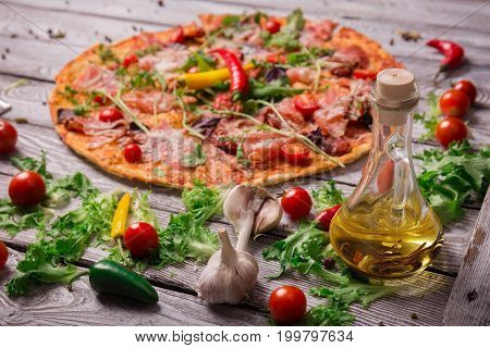 A close-up picture of a tasty margarita pizza with vegetables, bottle of olive oil and salad leaves. Delicious bright dish on a rustic table background. Italian cuisine. Cooking concept. Copy space.