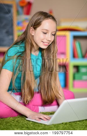 Cute little girl with modern laptop on floor