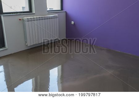 Interior of apartment under construction. Floor covering with self leveling plaster. Mirror smooth surface of the floor