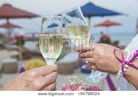 Bride and groom wedding couple holding a pair of champagne flute glasses in celebration on tropical beach