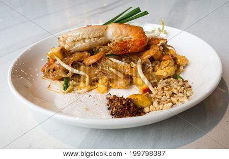 Fried Rice Sticks with Shrimp (PAD THAI GOONG SOD) put a white plate and placed on a white marble table.This is a popular food to eat when coming to Thailand.